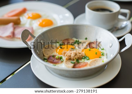 Breakfast egg dish served with fried egg, ham, orange juice, delicious. - stock photo