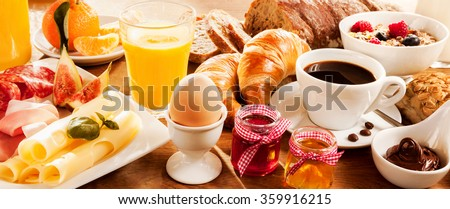 Breakfast feast with egg, meat, bread, coffee and juice - stock photo