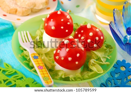 breakfast for child with fly agaric mushrooms made from boiled egg ,tomato and mayonnaise - stock photo