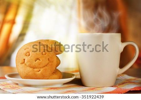 Breakfast for positive mood. A hot drink and biscuit with a smile - stock photo
