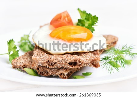 Breakfast fried egg on crispbread, close up view - stock photo