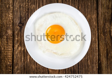 Breakfast (fried eggs) on an old wooden table (selective focus; close-up shot) - stock photo