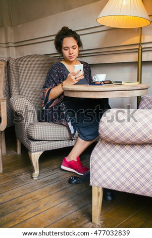 breakfast - girl sitting with smartphone and a cup of coffee at the cafe