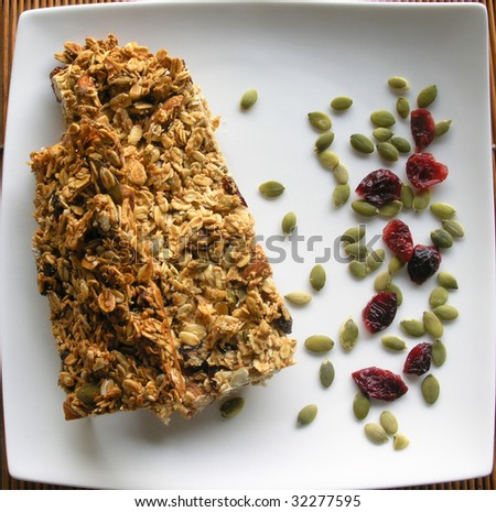 breakfast granola bars on a white squared plate sprinkled with pumpkin seeds and dried cranberries - stock photo