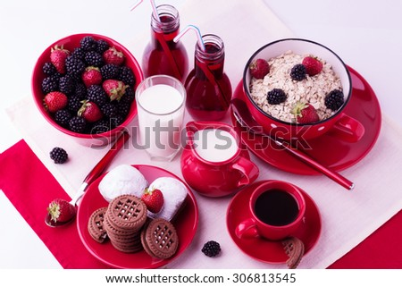 Breakfast - granola with blueberries and strawberries, coffee with milk and cookies isolated on white background.  Selective focus.