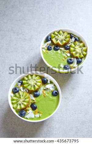 breakfast green smoothie bowl topped with kiwi, blueberry, coconutflake and bee pollen - stock photo