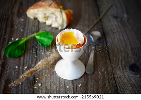 Breakfast image: soft boiled egg in white egg cup, green salad and ciabatta on dark wooden table - stock photo