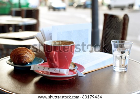 Breakfast in a Parisian street cafe - cup of coffee, croissant and book - stock photo