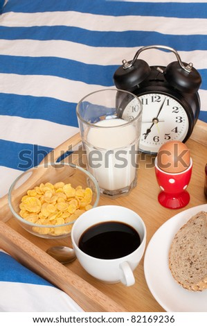 Breakfast in Bed - Bread, Coffee, Boiled Egg, Milk, Corn Flakes and Alarm Clock - stock photo