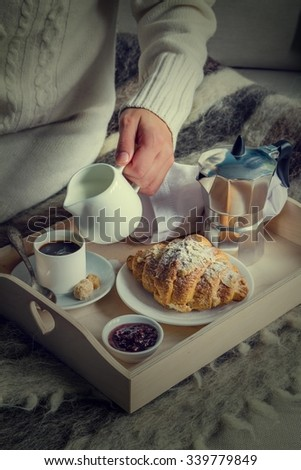 Breakfast in bed - female holding milk, coffee, croissant on tray, wool blanket, toned