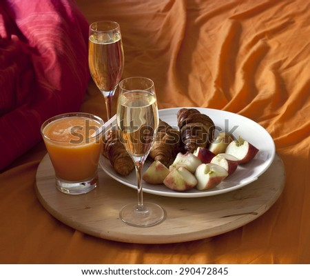 Breakfast in bed: two glasses of champagne, a glass of fresh pressed citrus juice, croissants and fresh peaches on a plate - stock photo