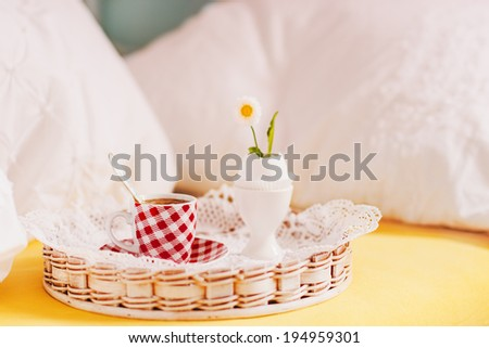 Breakfast in bed. With hot espresso and little flower in eggshell. Selective focus on cup. - stock photo