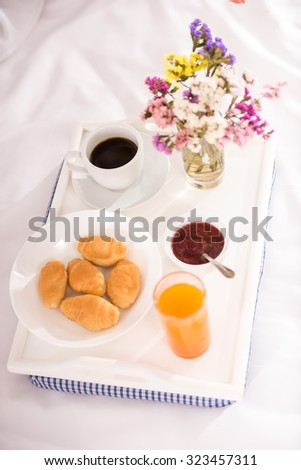 Breakfast in bed with pastries, coffee and flowers for your sweetheart on a tray - stock photo