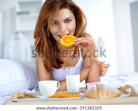 Breakfast in bed / woman eating healthy fruit in bed while happy and smiling  - stock photo