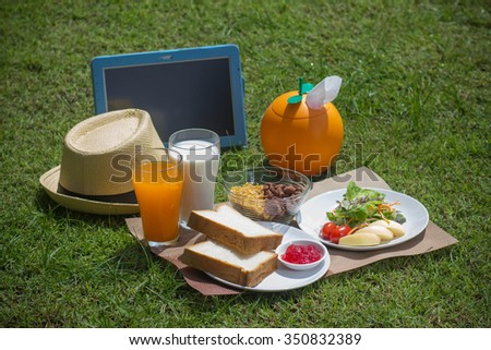 Breakfast in the garden with i-pad. - stock photo