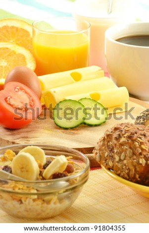 Breakfast including rolls, egg, cheese, coffee and orange juice on the table