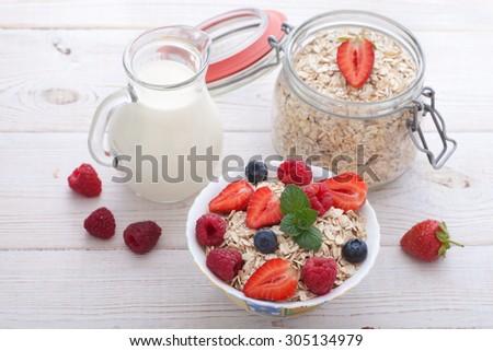 Breakfast. Ingredients for healthy breakfast - berries, fruit, milk and muesli on white wooden table, close-up top view horizontal. Macro shot selective focus - stock photo