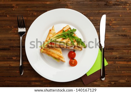breakfast is served. Classic White bread sandwich with chicken, cheese, tomatoes, green salad, decorated with arugula on a white plate - stock photo