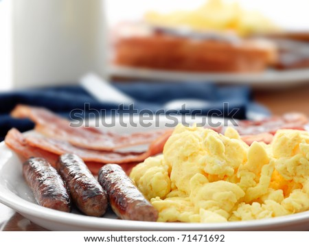 breakfast meal with sausage and scrambled eggs with bacon. - stock photo