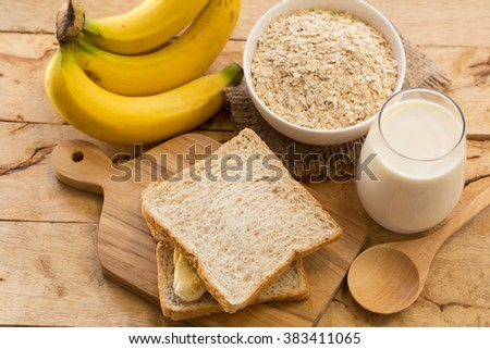 Breakfast milk, banana and bread on a wooden table. - stock photo