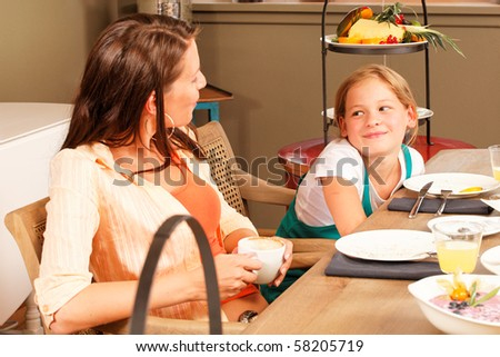 breakfast mother and daughter looking and talking to each other - stock photo