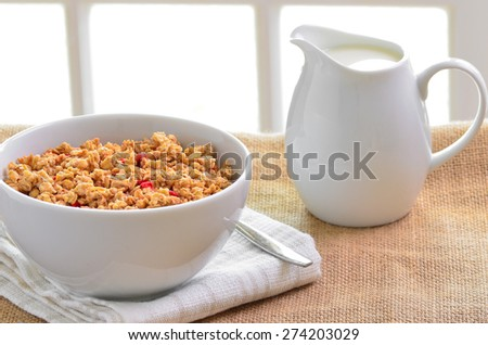 Breakfast Muesli cereal clusters with a jug of fresh milk. - stock photo