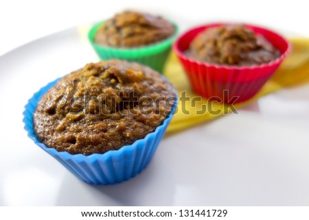 Breakfast muffins with dates, oats and pecans on a white plate with a yellow napkin in coloured silicone cases. - stock photo