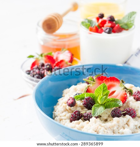 Breakfast - oatmeal, berries, mint, honey, white wood background