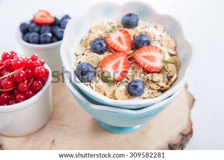 Breakfast: oatmeal cereals with selection of berries on the white wooden table, selective focus