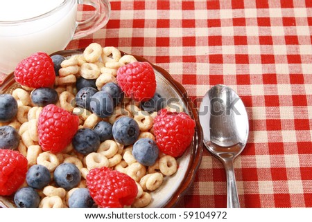 Breakfast of berries and milk on checkered tablecloth