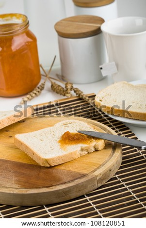 Breakfast of bread and jam on the table knife - stock photo