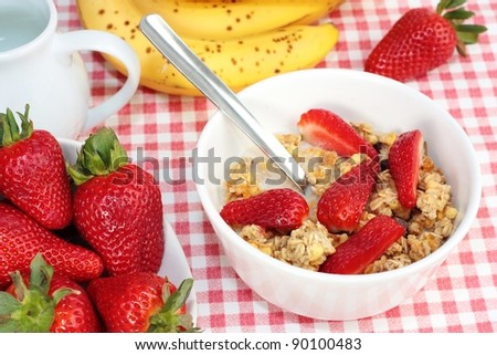 Breakfast of cereal, strawberries and bananas.