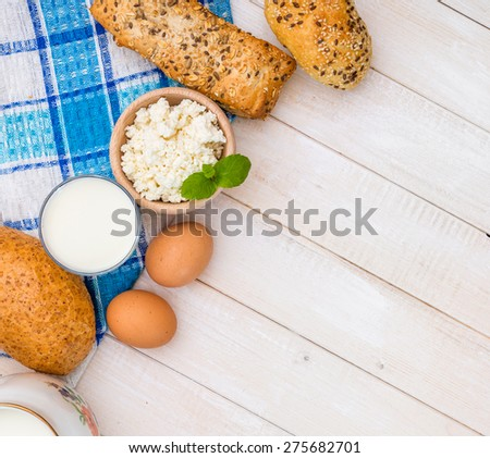 Breakfast of cheese, milk, bread and eggs on a light wooden background - stock photo