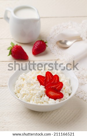 Breakfast of cottage cheese with fresh strawberries and cream jug - stock photo
