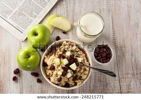 Breakfast of oatmeal cereal with cranberries and apples and a glass of milk and a newspaper