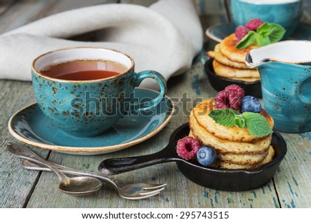 Breakfast of pancakes, fresh berries and black tea in rustic style - stock photo