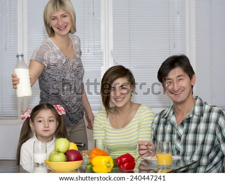 Breakfast of poly ethnic family.  Family of four people has breakfast. People of different nations - Caucasian and Asian, healthy food - fruits, colorful vegetables, juice and milk, modern lifestyle. - stock photo