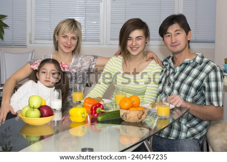 Breakfast of poly ethnic family.  Family of four people is having breakfast. Different ethnics - Caucasian and Asian, healthy food - fruits, colorful vegetables, juice and milk, modern lifestyle.