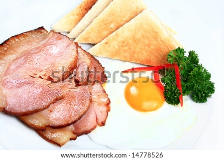 breakfast of sliced ham and eggs with toast
