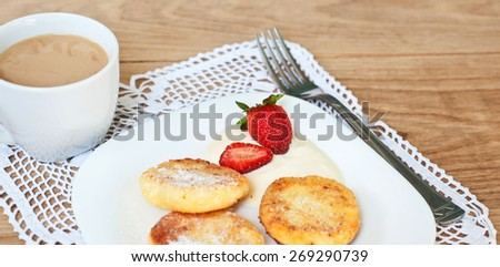 Breakfast of tasty round pancakes with cottage cheese with fragrant red ripe strawberries on a square white plate and coffee with milk cappuccino on wood desk - stock photo