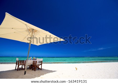 Breakfast on tropical white sand beach in Mauritius Island - stock photo