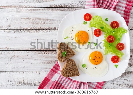 Breakfast on Valentine's Day - fried eggs and bread in the shape of a heart and fresh vegetables. Top view - stock photo