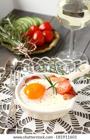 Breakfast on wooden tray, fried egg with bacon and vegetables - stock photo
