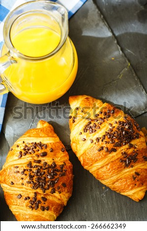 Breakfast, orange juice and fresh chocolate criossants on the table - stock photo