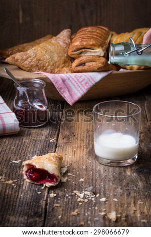 breakfast pastries with jam and milk on old wooden table, splash milk
