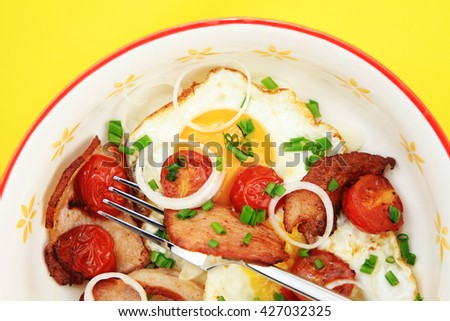 Breakfast plate - eggs with bacon, tomatoes, onion rings and herbs. Yellow background.