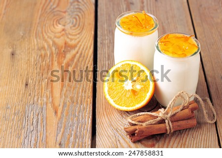 Breakfast products (homemade yogurt, orange and cinnamon jam) on a wooden table. Selective focus, copy space background - stock photo