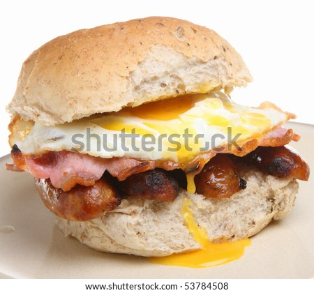 Breakfast roll with bacon, sausages and fried egg. - stock photo
