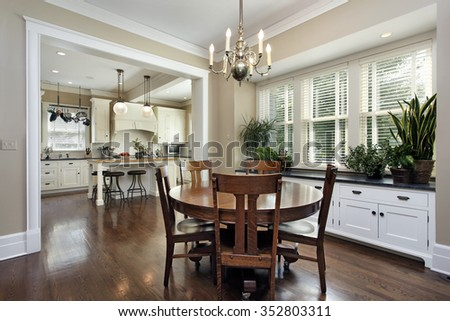 Breakfast room in luxury home with kitchen view - stock photo