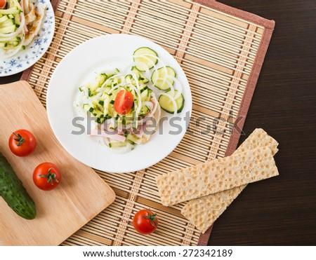 Breakfast. Salad with fried eggs, ham, cucumber, onion, tomatoes - stock photo